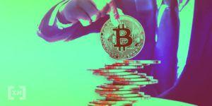 Mann im Anzug hält eine physische Bitcoin Münze auf einem Stapel von Münzen